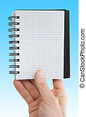 hand with blank paper notebook