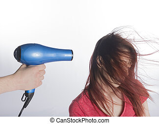 Hand with Blow Dyer Drying Long Hair of a Woman