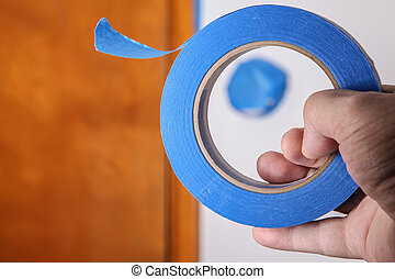 Hand with blue masking tape