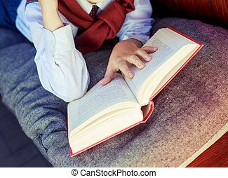 hand with book - hands of a boy with a book on the bench