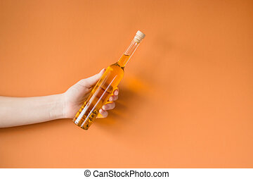 Hand with bottle of cooking oil isolated on a colored background