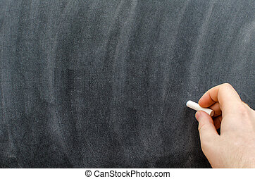 Hand with chalk writting on blackboard