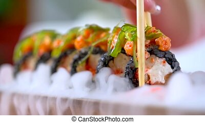 Close-up motion of woman's hand taking sushi rolls with tobiko, served in smoke, by wooden chopsticks at japanese restaurant. Getting familiar with japanese cuisine. Evening gastronomic leisure.