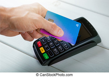 hand with credit card making contactless payment transaction