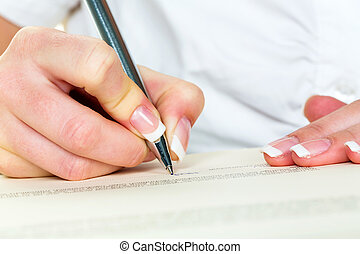 hand with fountain pen signing contract - a woman signs a ...