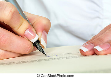 hand with fountain pen signing contract - a woman signs a...