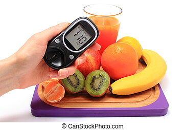 Hand with glucometer, fresh natural fruits, glass of juice