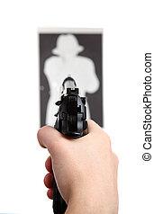 hand with gun shooting target