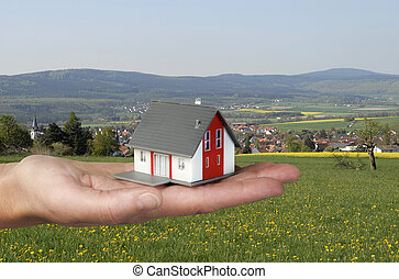 Hand with house in front of landscape - Hand holding an...