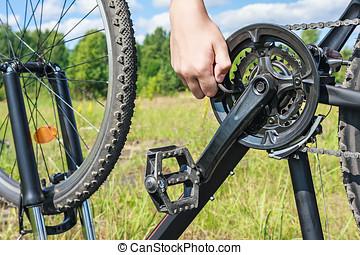 hand with key repairs bike