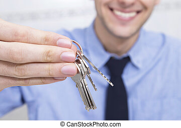 hand with keys and businessman smiling