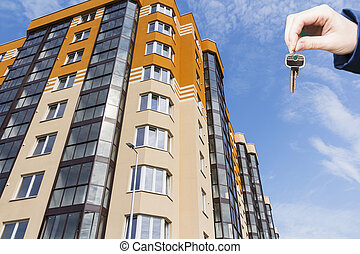 Hand with keys in the background apartment building.