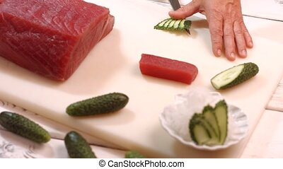 Hand with knife cuts cucumber.