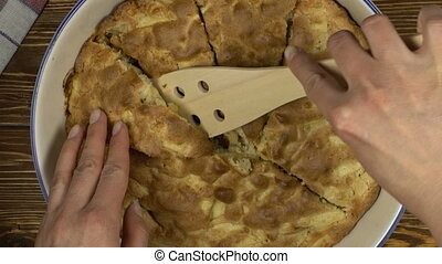 Hand with knife cutting appe pie on wooden desk and...