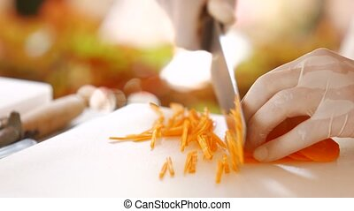 Hand with knife cutting carrot.