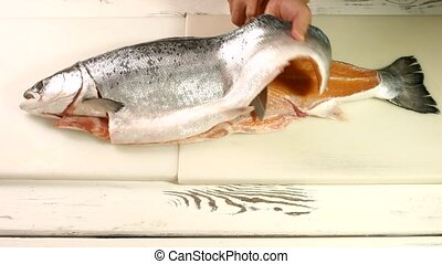 Hand with knife cutting fish.