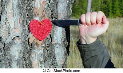 Hand with knife near fabric heart