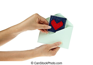 Hand with knitting red heart isolated on white background