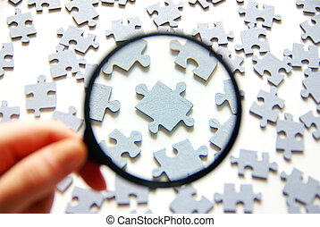 magnifying glass - Hand with magnifying glass and puzzle ...