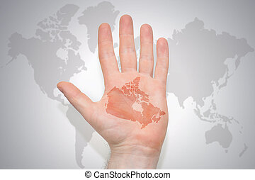 hand with map of canada on the gray world map background.