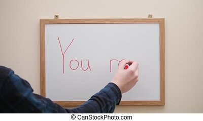 Hand with marker writing and erasing inscription You rock on white board