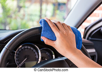 Hand with microfiber cloth cleaning Interior and steering wheel modern car.
