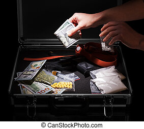Hand with money, gun and drugs