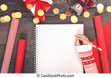 Hand with notepad Christmas tree and red gift wrapping paper