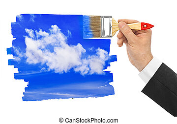 Hand with paintbrush drawing sky