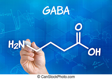 Hand with pen drawing the chemical formula of GABA