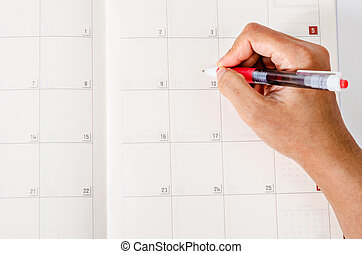 Hand with pen on calendar page.