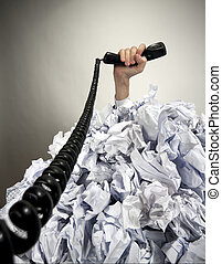 Hand with phone reaches out from heap of papers