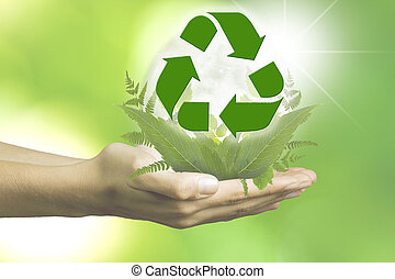hand with plants and the recycling symbol