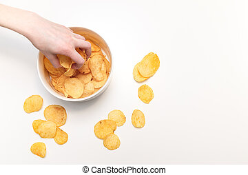 Hand with potato chips and bowl on white background
