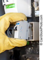 Hand with protecting safety gloves of electrician at electric meter or switch board at house exchanging fuse.
