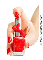 Hand with red manicure and nail polish bottle