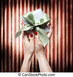 Hand with red nails holding a gift box