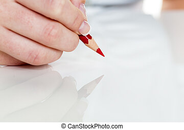 hand with red pencil - a hand is holding a red pencil....