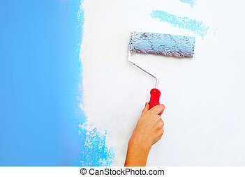 Hand with roller brush painting wall.