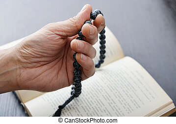 Hand with rosary beads