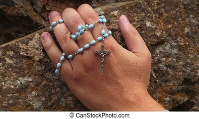 Hand with rosary on stone wall