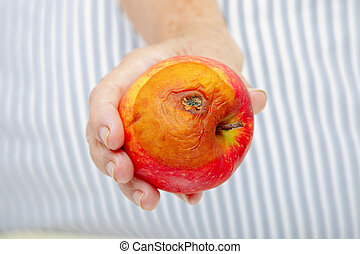 hand with rotten apple