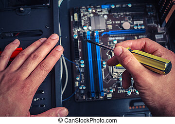 Hand with screwdriver installing computer