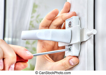 Hand with screwdriver tightens fixing screw of window  restrictor.