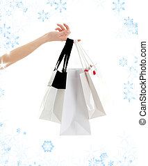 hand with shopping bags and snowflakes - hand with three ...