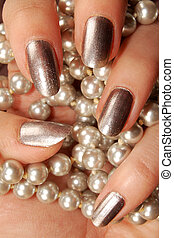 Hand with silver nails holds a pearl necklace.