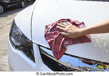 hand with soft clothes washing passenger car at home