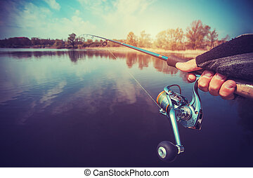 hand with spinning and reel on the evening summer lake