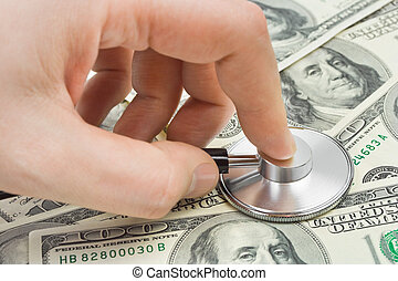 Hand with stethoscope and money - medical background