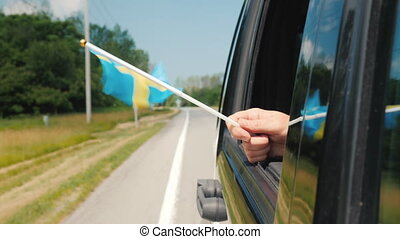 Hand with Sweden flag in a car window. Travel Scandinavia ...